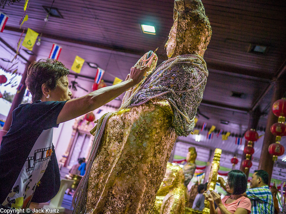 12 OCTOBER 2012 - RAI KHRING, NAKHON PATHOM, THAILAND:  Thai Buddhists apply gold leaf to a Buddha statue to make merit at Wat Rai Khring in Nakhon Pathom province. Wat Rai Khring was built in 1791, the Abbot at the time, Somdej Phra Phuttha Chan (Pook), named this temple after the district. When construction was completed, the Buddha image was brought from another temple and enshrined here. Later locals named the image ?Luang Pho Wat Rai Khing?. The Buddha image is of Chiang Saen style and is assumed to have been built by Lanna Thai and Lan Chang craftsmen.     PHOTO BY JACK KURTZ