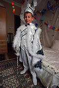Newly circumcised, a nine-year-old boy who lives in a suburb of Istanbul, Turkey, proudly poses in his sultan outfit, which is the customary attire at circumcision. He stands beside his bed which his parents have worked hard to make fit for a sultan.