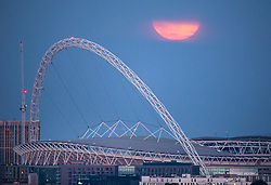 © Licensed to London News Pictures. 07/05/2020. London, UK. The Supermoon makes a brief appearance as it rises over Wembley Stadium in London. Also know as the Flower Moon at this time of year a supermoon is a full or new moon that comes closest to the Earth in its elliptical orbit—resulting in a slightly larger than usual apparent size when viewed from Earth. Photo credit: Peter Macdiarmid/LNP