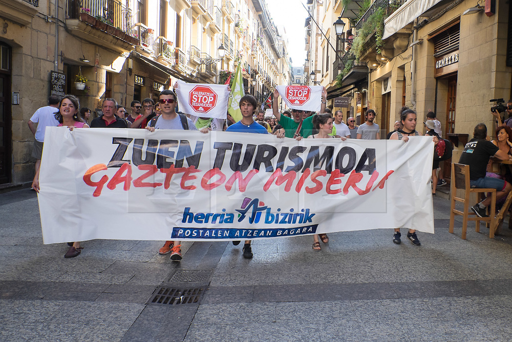 """@Licensed to London News Pictures 17/08/17. San Sebastian, Basque Country, Spain. Protestors leading an anti-tourism march today through the crowded streets of the Basque town of San Sebastian in Spain. The banner translation from Basque is """" Your tourism is the misery of the young"""". Following on from similar demonstrations in Barcelona protestors in San Sebastian are protesting against the  over-tourism of their country.  Photo credit: Manu Palomeque/LNP"""