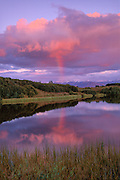 rainbow reflected in calm lake with crimson clouds, blue sky and mountains.