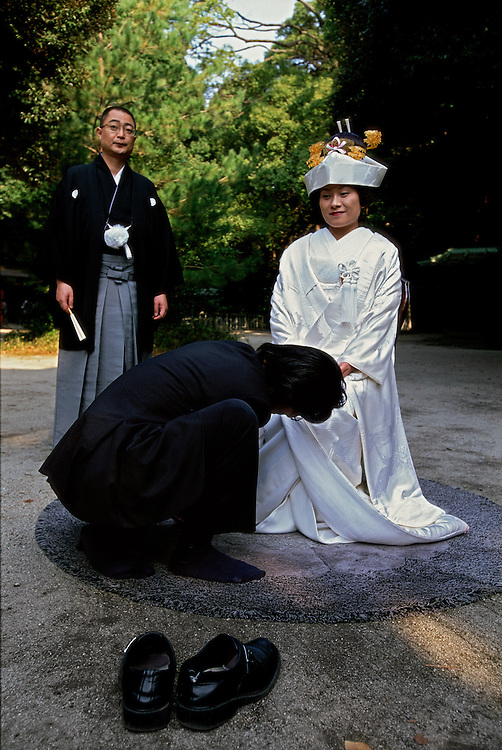 Photographing the bride and groom at a traditional Shinto wedding at the Meiji shrine in Tokyo, Japan. The photographer helps the bride adjust her kimono.
