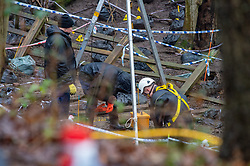 © Licensed to London News Pictures. 17/12/2019. Beaconsfield, UK. A member of the search team wearing a dry suit and a harness kneels below a tripod hoist stand and looks in to an ingress point to what appears to be an underground area. London's Metropolitan Police Service have called in the forces specialist Under Water and Confined Space Search Team as they continue to search woodland in Beaconsfield. The Met confirmed on 12th December 2019 they are searching the woodland in Beaconsfield, Buckinghamshire in connection with the disappearance and murder of Mohammed Shah Subhani. Police have been in the area conducting operations on Hedgerley Lane since Thursday 5th December 2019 and are combing wooded area with specialist officers assisted by specialist search dogs. Photo credit: Peter Manning/LNP