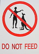 """Do not feed"" the kangaroos is shown symbolically on a red-orange sign in Australia."
