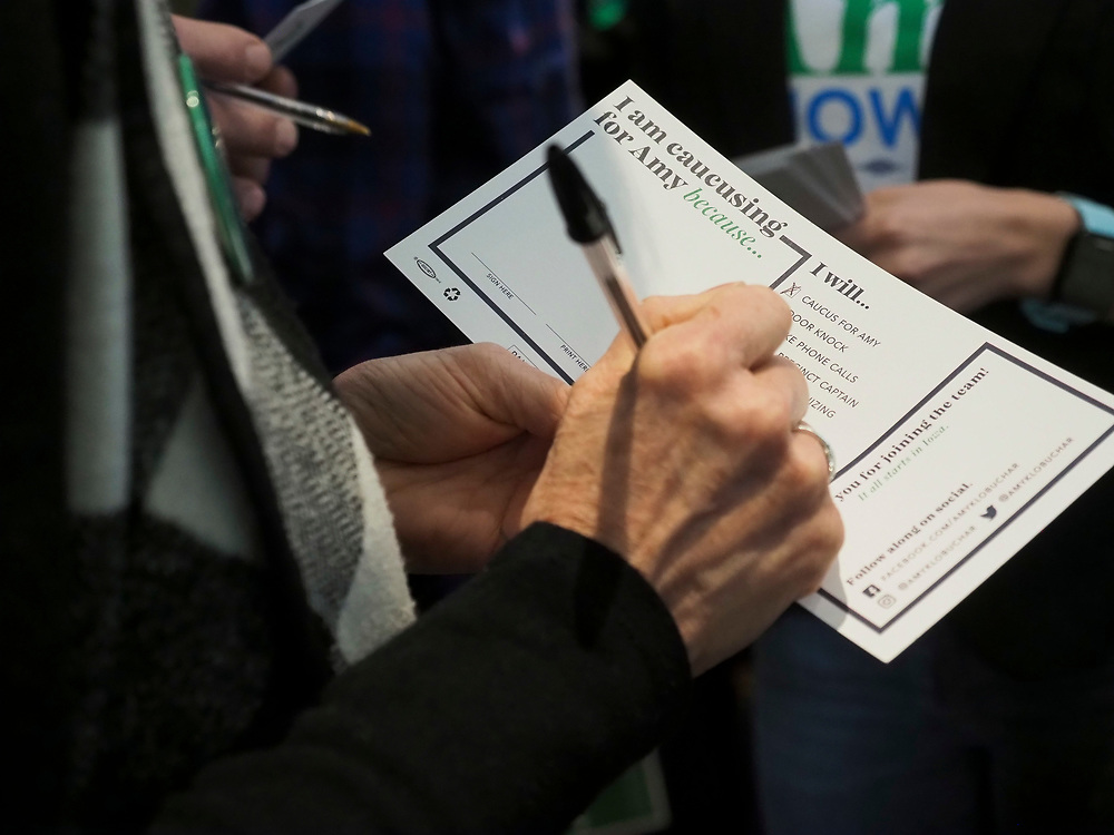 An Amy Klobuchar supporter signs a pledge card to support her during the upcoming caucus.