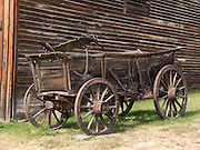 "A wagon with iron-bound wooden wheels stands outside a late 1800s livery stable preserved at the outdoor history museum of Nevada City, Montana, USA. Nevada City was a booming placer gold mining camp from 1863-1876, but quickly declined into a virtual ghost town. This fascinating town inspires you to imagination what life must have been like in early Montana when gold was discovered at nearby Alder Gulch. More than 90 buildings from across Montana have been gathered for preservation at Nevada City, mostly owned by the people of the State of Montana, and managed by the Montana Heritage Commission. In 2001, the excellent PBS television series ""Frontier House"" used one of the buildings and its furnishings to train families in re-creating pioneer life. A miner's court trial and hanging of George Ives in the main street of Nevada City was the catalyst for forming the Vigilantes, a group of citizens famous for taking justice into their own hands in 1863-1864. Directions: go 27 miles southeast of Twin Bridges, Montana on Highway 287."