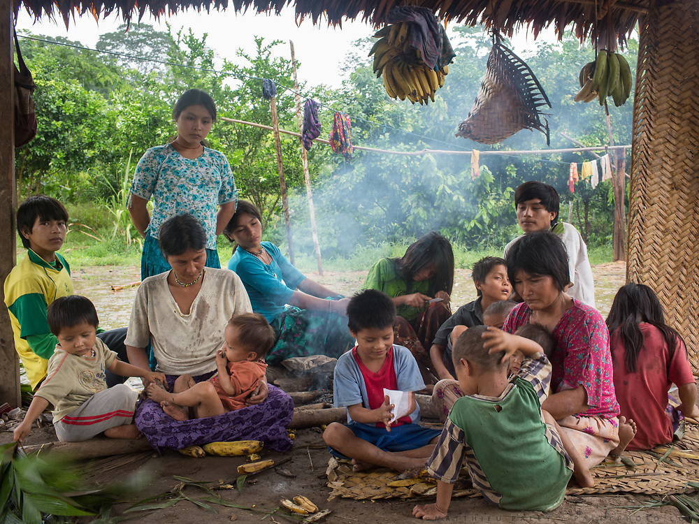 While the men are out hunting, the women and children of the Nate family sit around the fire in the outise kitchen and eat Plantain, the staple food, hoping for meat to be brought back.