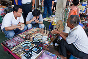 Mar. 7, 2009 -- BANGKOK, THAILAND:  Men shop for religious amulets in the amulet market in Bangkok, Thailand. The Amulet Market is adjacent to Wat Mahathat, between Maharat Road and the river. It is Bangkok's biggest amulet market, where a fantastic array of religious amulets, charms, talismans, and traditional medicine is sold. Photo by Jack Kurtz / ZUMA Press