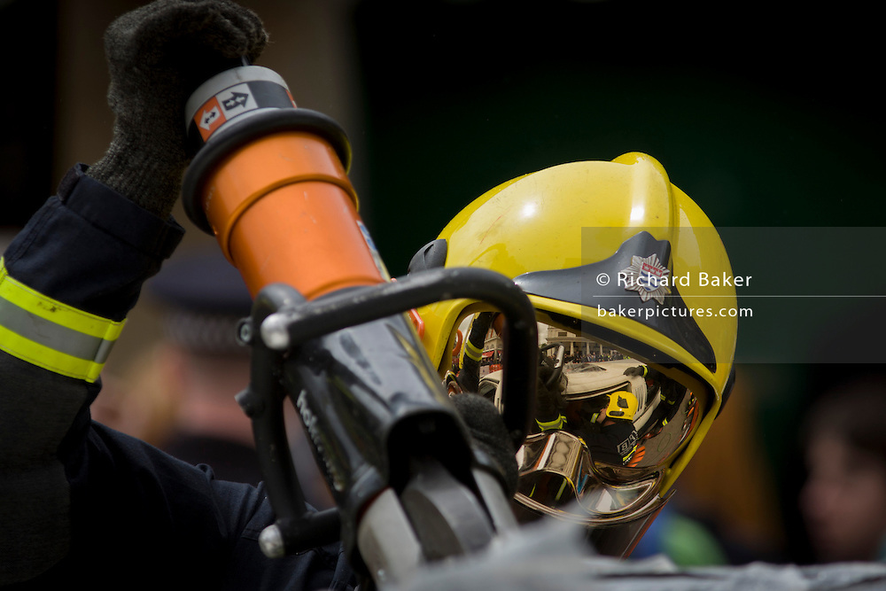 Firefighter from the London Fire Brigade's 'extrication' team using a using a Holmatro dedicated cutter to give a demonstration on how firefighters rescue passengers by cutting open a stretch limousine in London's Covent Garden Piazza. Highlighting the dangers of hiring illegal luxury or novelty cars, this vehicle was seized last year with many mechanical defects rendering it unsafe for those inside with limited exit doors. Of 358 cars stopped in March 2012, 27 were seized and 232 given prohibitions. This scenario is a simulation and therefore reproduces the reality of an emergency, using real emergency services personnel and equipment. Casualties are volunteers and none were injured in the making of this photograph.