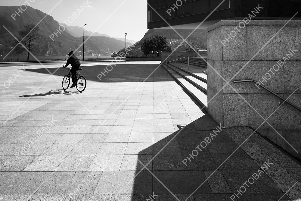 A man rides a bicycle in a large square. Black and white photos