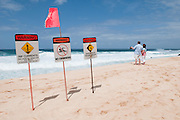Two people looking at the ocean with Beach Warning Signs.