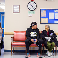 Brannon Holtsoi, center, sits with her grandmother Mary Holtsoi after completing the Turkey Trot 5k run Friday at the Coyote Canyon Chapter House.