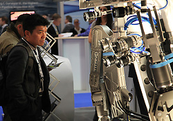 © Licensed to London News Pictures. 11/03/2014. London, UK. A man looking at the manipulator of a work-class Remote Operated Vehicle (ROV). Oceanology International (OI), the world's largest exhibition for marine science and technology, gets underway at London's ExCeL Centre. The three day exhibition provides an opportunity for industry, academic and government organisations to share knowledge and promote improvements in technology and strategy used for operating, surveying, protecting and exploiting resources in the oceans of the world. Photo credit : Rob Arnold/LNP