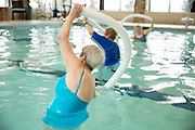 Senior women doing water aerobics with pool noodle