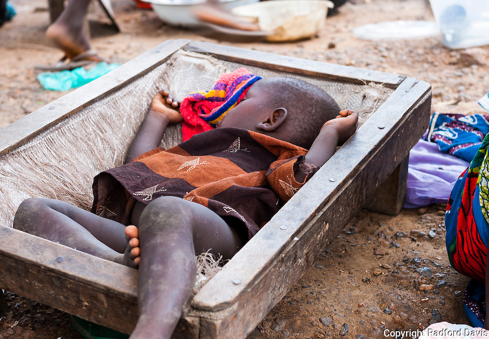 A child sleeps peacefully in this ingenious portable bed. The family was sitting along the road to the Doctors Without Borders hospital, selling fruit and other items. Kids are often the ones bitten by dogs, so educating them and their parents about dogs, behavior around dogs, and what to do if bitten are important aspects in preventing rabies.
