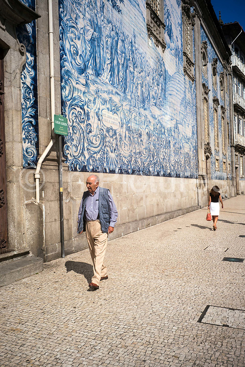 An man walks past the Capela Das Almas in Porto, Portugal. The church is clad in ornate azulejo tiles that depict scenes from the lives of various saints, including the death of St Francis and the martyrdom of St Catherine.