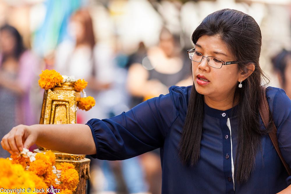 """20 MAY 2104 - BANGKOK, THAILAND: A woman prays at Erawan Shrine in Bangkok after the Thai army declared martial law. The Thai Army declared martial law throughout Thailand in response to growing political tensions between anti-government protests led by Suthep Thaugsuban and pro-government protests led by the """"Red Shirts"""" who support ousted Prime Minister Yingluck Shinawatra. Despite the declaration of martial law, daily life went on in Bangkok in a normal fashion. There were small isolated protests against martial law, which some Thais called a coup, but there was no violence.   PHOTO BY JACK KURTZ"""
