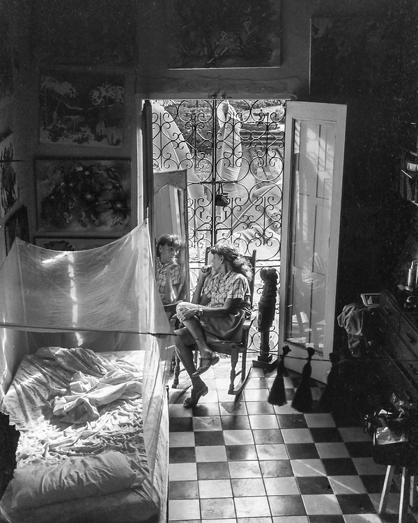 Irene Ballesteros (wife of Spanish surrealist painter, Esteban Frances) looking in the mirror with her paintings above her in San Juan, Puerto Rico  (1987)