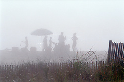 Spectral figures obscured by heavy fog set up early on the beach in front of the boardwalk in Rehoboth Beach, Del., Saturday, Aug. 17, 2019. (Photo by D. Ross Cameron)