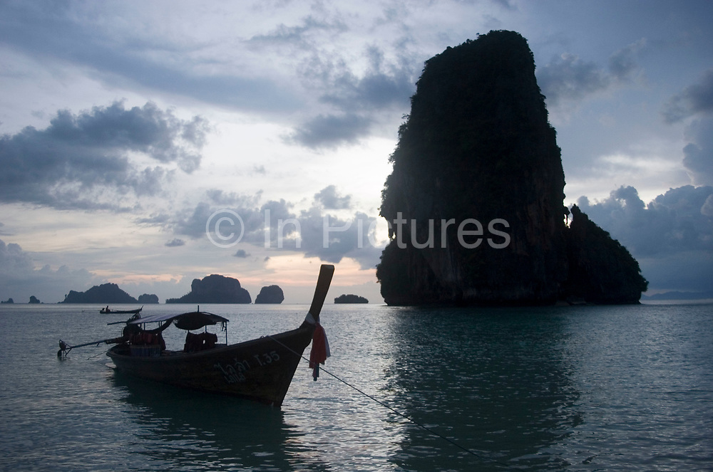 Longtail boat at sunset at Phra Nang Bay, Railay. This pure white sand beach is surrounded by spectacular limestone cliffs. Central in the bay stands Phra Nang's distinctive rock, looming over the bay dramatically.