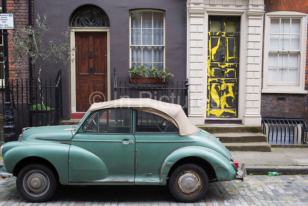Vintage Morris Minor with a soft top outside a house with a peeling paint door in Spitalfields, London, UK. The Morris Minor is a British economy car that debuted on 20 September 1948. Designed under the leadership of Alec Issigonis, more than 1.3 million were manufactured between 1948 and 1972. Initially available as a two-door saloon, the range was subsequently expanded to include a convertible version.