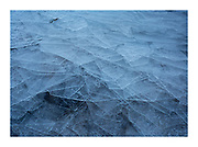 fragments of sea ice stacked on top of each other looking like broken glass.  Washed up by waves into wave like patterns