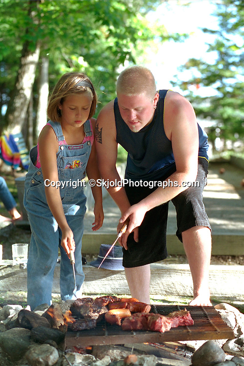 Cousins barbecuing over outside pit on family vacation ages 23 and 9.  Cedarville  Michigan USA