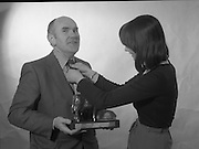 1980-02-19.19th February 1980.19-02-1980.02-19-80..Something of a Tie:..Photographed at: location unspecified..Frank Flanagan, Chairman of National Dairy Council and Irene Cunningham, Ranks (I) Ltd,  admiring the Bronze Cow Trophy  due to be awarded at the Munster Dairy Farmer of the Year event. The trophy is tje work of Rowan Gillespie who is also responsible for the GAA All Star trophies.