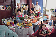 """(MODEL RELEASED IMAGE) The Sobczynscy family in the main room of their apartment in Konstancin-Jeziorna, Poland, outside Warsaw; with a week's worth of food. Marzena Sobczynska, and Hubert Sobczynski stand in the rear; with Marzena's parents; Jan Boimski, and Anna Boimska; to their right and their daughter Klaudia on the couch. (Polish surnames are gender-based and can change when speaking of the family as a whole. """"Sobscynscy"""" is plural). The Sobczynscy family is one of the thirty families featured in the book Hungry Planet: What the World Eats (p. 246)."""