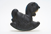 a little plastic rocking horse toy covered with black paint