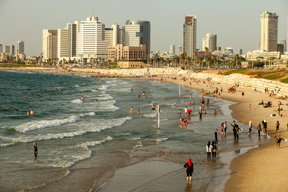 People are seen at the Charles Clore Beach in Tel Aviv