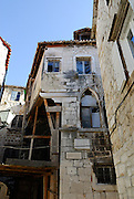 Section of old building subsiding and cracking, with timber bracing holding it up. Trogir, Croatia