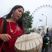 First Nation woman Kiera Dawn-Kolson sing a traditional song outside Shell HQ to change their spirit and hearts and get out of her ancestors land in Canada. The giant polar bear puppet Aurora made by Greenpeace walked the streets of London in defence of the Arctic as part of a Greenpeace global day of action. The parade,part performance part protest, was to highlight the melting ice caps and the increasing and potentially devastating oil drilling in the arctic sea. Shell is one of the companies drilling and the march through London ended up outside Shell London HQ to draw attention to their oil business in the arctic. Aurora, the biggest polar bear in the world represents all endangered species in arctic.