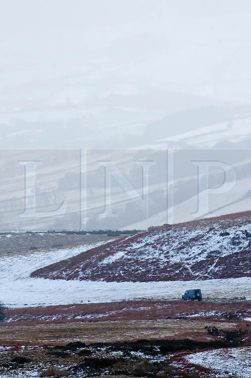 © Licensed to London News Pictures. 13/02/2014. Mynydd Epynt Uplands, Powys, wales, UK. A four wheel drive vehicle drive along a narrow road. Temperatures dropped below zero and a light dusting of snow fell last night on high land in Mid Wales and in The Brecon Beacons National Park. Hailstorms replaced snowfalls this morning. Photo credit : Graham M. Lawrence/LNP