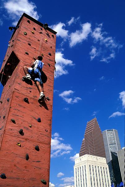 Stock photo of a boy scaling an outdoor rock climbing tower near downtown Houston, Texas