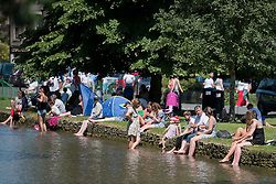 © Licensed to London News Pictures. 19/07/2016. BOURBON ON THE WATER, GLOUCESTERSHIRE, UK.  Cooling off by the river Windrush  to cool off. Hottest day of the year in Bourton on the Water in Gloucestershire..  Photo credit: MARK HEMSWORTH/LNP