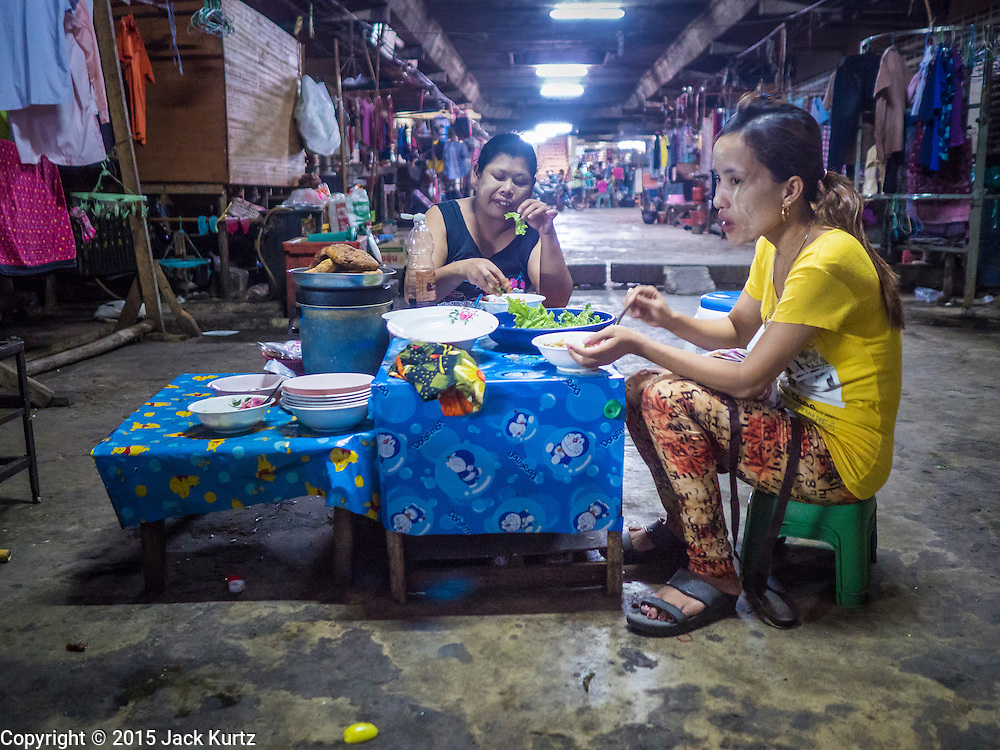 "11 JUNE 2015 - MAHACHAI, SAMUT SAKHON, THAILAND:   Burmese migrant workers eat their lunch in the bottom floor of a tenement building used for migrant housing in Mahachai. Labor activists say there are about 200,000 migrant workers from Myanmar (Burma) employed in the fishing and seafood industry in Mahachai, a fishing port about an hour southwest of Bangkok. Since 2014, Thailand has been a Tier 3 country on the US Department of State Trafficking in Persons Report (TIPS). Tier 3 is the worst ranking, being a Tier 3 country on the list can lead to sanctions. Tier 3 countries are ""Countries whose governments do not fully comply with the minimum standards and are not making significant efforts to do so."" After being placed on the Tier 3 list, the Thai government cracked down on human trafficking and has taken steps to improve its ranking on the list. The 2015 TIPS report should be released in about two weeks. Thailand is hoping that its efforts will get it removed from Tier 3 status and promoted to Tier 2 status.      PHOTO BY JACK KURTZ"