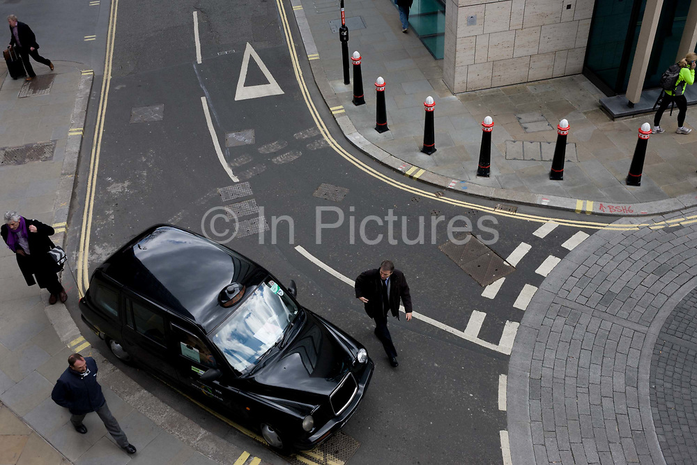 Seen from a high walkway above, we see an aerial landscape of city road markings and roundabout junction. As pedestrians walk-by, a licensed black taxi cab has parked on the edge of a mini roundabout, awaiting a named passenger to emerge from a nearby office - the person's name is written on a board hanging from the vehicle's window. The curves and linear landscape of this cityscape, arc into the distance and Corporation of London bollards are freshly painted.