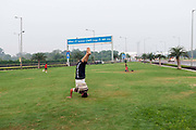 A man practices yoga on the private traffic greens at Aerocity near Terminal 3 of Indira Gandhi Airport, New Delhi, India