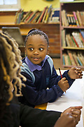 A young African school-girl talks to her teacher during a writing exercise in a classroom in Prestwich Primary School, Green Point, Cape Town, South Africa. She is holding a pencil and has been writing in her exercise book.