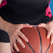 A woman holding a basketball, posed as if she is about to pass or shoot. Photographed with studio lights in front of a blue backdrop. No visible logos or brandmarks in this photo.