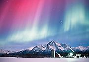 Alaska. Palmer. Northern Lights. Aurora Boreali glow above a barn in the Matanuska Valley.