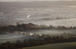 © Licensed to London News Pictures. 05/03/2014. Butser Hill, Hampshire, UK. A misty sunrise across Petersfield, today 5th February 2014. Photo credit : Rob Arnold/LNP