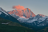 Sunset strikes the high peaks, and a cloud forms above them to catch the last bit of the day as well.