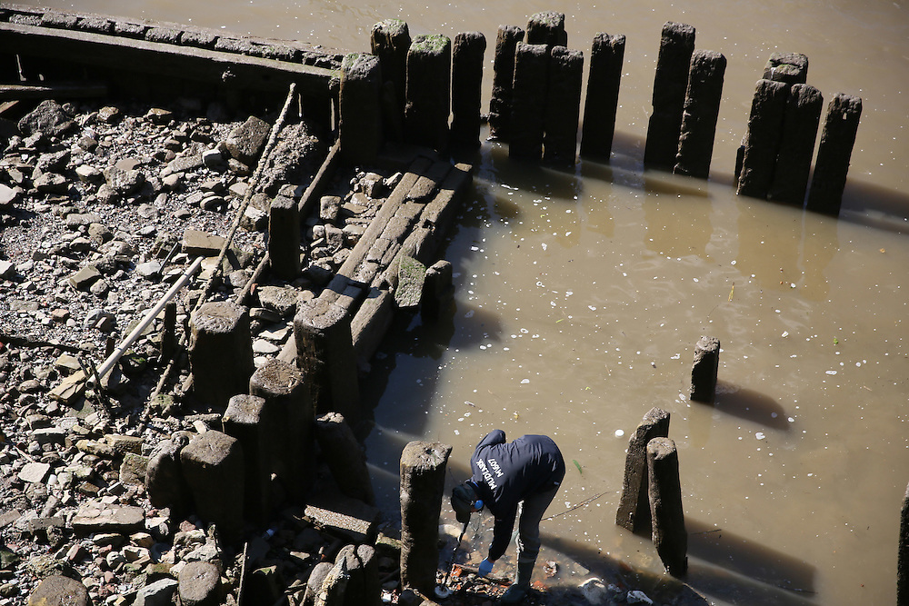 Mudlarker Matthew Goode looks for items on the banks of the River Thames in London, Britain May 23, 2016. When the river Thames is at low tide, mudlarkers scour the shore for historical artefacts and remains from there City of London's ancient past. Finds can date back to Roman times to when the city was found up until more recent times. Anyone can walk along the river and look for finds, but the uses of metal detectors and digging is restricted. Mudlarkers need to be licences by the Port of London Authority. All find should be register with the Museum of London. REUTERS/Neil Hall