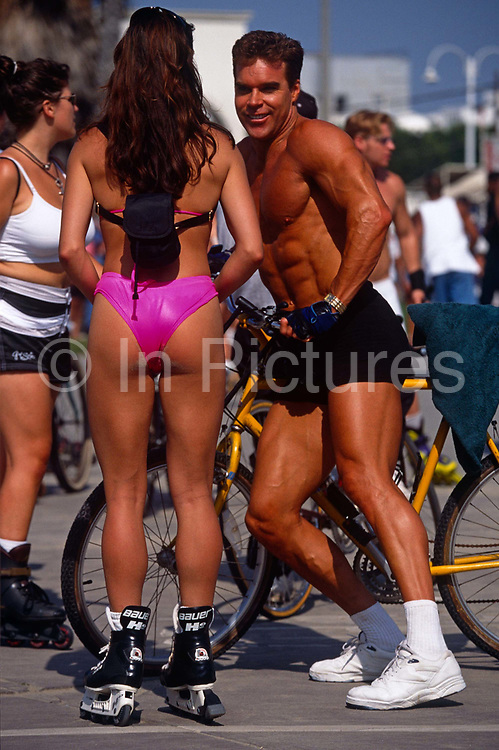 Wearing beachwear and topless in shorts are the beautiful people of Los Angeles' famous Venice Beach. A dashing athletic male specimen, all six-pack muscles, a dark tan with white trainers, socks and leaning on a bike, flirts with a young woman whose perfect body is facing away from us, allowing us a peek at her bottom and long, slender legs and rollerblades. She wears a very small pink bikini and a tiny back-pack in the west coast sunshine. There is sexuality and machismo here between the sexes where exhibitionists and extroverts display their confidence and talents, the guy's body language showing and facial expression giving off a keen interest in this woman's female form.