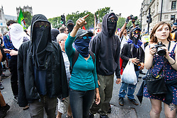 © Licensed to London News Pictures. 14/07/2018. London, UK. PICTURED: ANTI FASCIST PROTESTERS block pro Robinson/Trump supporters . Supporters of EDL founder Tommy Robinson ( real name Stephen Yaxley-Lennon ) and US President Donald Trump and anti fascists clash on Westminster Bridge during a day of demonstrations and rallies in support and opposed to US President Donald Trump and jailed EDL founder Tommy Robinson . Trump is currently in Scotland and Robinson is in HMP Hull . Photo credit: Joel Goodman/LNP
