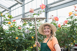 Mature woman holding rake and smiling in garden centre, Augsburg, Bavaria, Germany