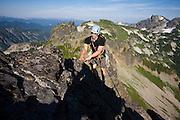 Climber Ian Derrington on the narrow summit ridge of Pinnacle Peak during a traverse of the Tatoosh Range in Mount Rainier National Park, Washington.