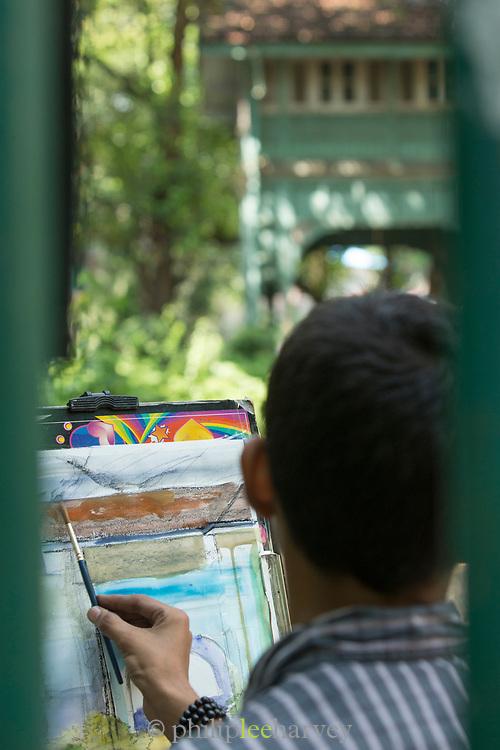 Close-up of art student paints Rudyard Kipling's Bungalow, Mumbai, India